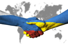 Russian flag and Ukraine flag across handshake. Stock Images