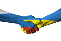 Russian flag and Ukraine flag across handshake. Royalty Free Stock Image