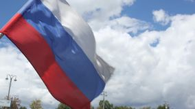 Russian flag waving from wind against green trees and city flashlights