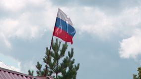 Russian flag in the wind against the summer blue sky. Russian flag in the wind on the background of the summer blue sky in burepolom stock video