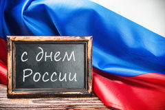 Russian flag on a wooden table and a blackboard with the text Stock Images