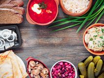 Russian food assortment. Russian food on wooden background. Assortment dishes of Russian cuisine - borscht, pelmeni, herring, marinated mushrooms, salted stock photography