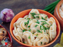 Russian food pelmeni. Closeup view of traditional russian food - pelmeni, ravioli or meat dumplings - on brown wooden table. Served with marinated mushrooms stock images