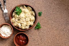 Russian food pelmeni meat dumplings with sour cream and tomato sauce. Top view, flat lay,copy space.  royalty free stock photography