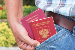 Russian and German passports in hand. Of man Stock Photo