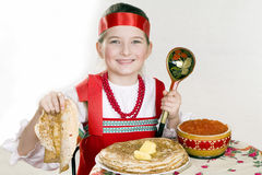 Russian  girl  behind a table with pancakes Stock Photos