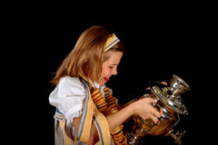 Russian girl eating bagels and drinks tea from a samovar Stock Images
