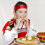 Russian girl eats pancakes with red caviar. Royalty Free Stock Photos