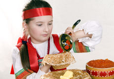 Russian girl eats pancakes with red caviar. Royalty Free Stock Image