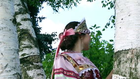 Russian girl in folk costume dreams with birch stock footage