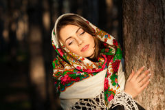 Russian girl in headscarves near the tree in the forest Royalty Free Stock Photo