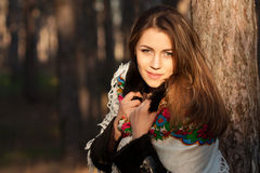 Russian girl in headscarves near the tree in the forest Royalty Free Stock Photos