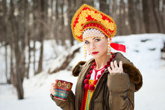 Russian girl in a kokoshnik. Russian girl drinking tea outdoors in the village stock photos