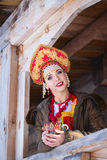 Russian girl in a kokoshnik. Russian girl drinking tea and smiling stock photography