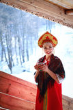 Russian girl in a kokoshnik. Russian girl drinking tea and smiling royalty free stock image