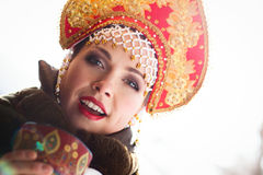Russian girl in a kokoshnik. Russian girl drinking tea and smiling royalty free stock images
