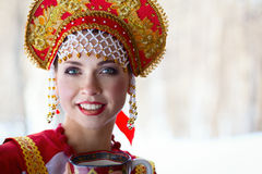 Russian girl in a kokoshnik. Russian girl drinking tea and smiling stock image