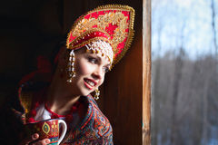 Russian girl in a kokoshnik. Russian girl drinking tea and smiling Royalty Free Stock Photos