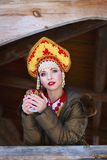 Russian girl in a kokoshnik. Russian girl drinking tea in the village Stock Photography