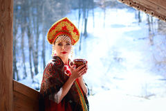 Russian girl in a kokoshnik. Russian girl drinking tea in the village royalty free stock photos