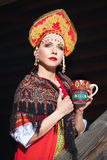 Russian girl in a kokoshnik. Russian girl drinking tea in the village Royalty Free Stock Images