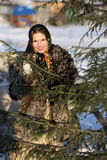 Russian girl in national dress. A girl in a fur coat and scarf. Russian village. Winter Stock Photography