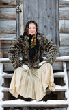Russian girl in national dress. A girl in a fur coat and scarf. Russian village. Winter Royalty Free Stock Photos