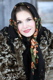 Russian girl in national dress. A girl in a fur coat and scarf. Russian village. Winter Stock Photo