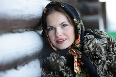 Russian girl in national dress. A girl in a fur coat and scarf. Russian village. Winter Royalty Free Stock Photography
