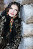 Russian girl in national dress. A girl in a fur coat and scarf. Russian village. Winter Royalty Free Stock Images
