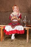 Russian girl in national dress. Young girl in Russian national suit eats pancakes with sour cream Stock Image