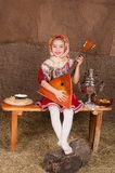 Russian girl in national dress. Young girl in Russian national suit playing a stringed instrument Royalty Free Stock Photography