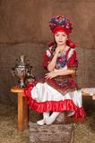 Russian girl in national dress. Young girl in Russian national suit sitting on a bench Stock Photo