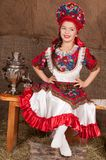 Russian girl in national dress. Young girl in Russian national suit sitting on a bench Royalty Free Stock Photo