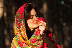 Russian girl in national headscarves with apple Royalty Free Stock Image