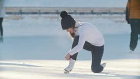 Russian girl skater skating, falling and standing up on a public ice rink. Youth pastime and res stock video