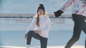Russian girl skater skating, falling and standing up on a public ice rink. Youth pastime and res stock footage