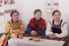Russian girl in traditional costume. Sitting at the table Stock Photography