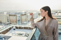 Portrait of beautiful blond young woman standing in bathrobe on terrace outdoor with city scape. Russian girls do not afraid neither cold or frost. Brave royalty free stock image