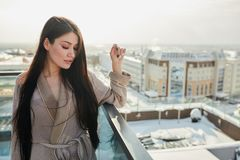 Portrait of beautiful blond young woman standing in bathrobe on terrace outdoor with city scape. Russian girls do not afraid neither cold or frost. Brave royalty free stock photo