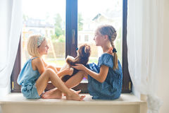 Russian girls sitting near window at home playing teddy bear. Two cute russian toddler girls sitting near window at home playing teddy bears happy and funny Stock Photography