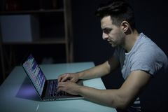 Caucasian hacker hacking the server in the dark. Russian hacker hacking the server in the dark Royalty Free Stock Photography