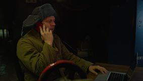 Russian hacker for laptop. Russian hacker in hat with earflaps working behind a laptop stock video