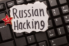 Russian hacking, inscription on torn paper sheet. Russian hacking, inscription on torn white paper sheet, on a keyboard stock photos