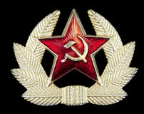 Russian Hammer and Sickle Badge. Pin badge with Russian hammer and sickle in a star-shape, surrounded by golden feathers. Isolated on black royalty free stock images