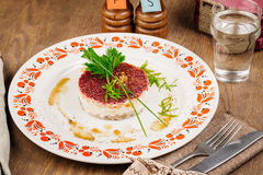 Russian herring salad on plate on wooden table Stock Image