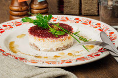 Russian herring salad on plate on wooden table Royalty Free Stock Photos