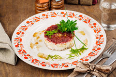 Russian herring salad on plate on wooden table Stock Photo