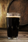 Russian Imperial Stout in pint glass on wood background and barr Royalty Free Stock Photography