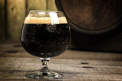 Russian Imperial Stout in snifter glass on wood background and b Royalty Free Stock Images